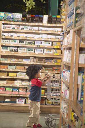 Boy pushing a shopping cart in a supermarket Stock Photo - 16071558