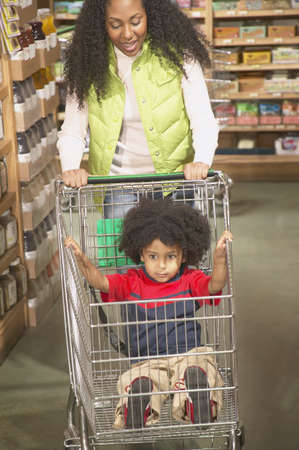 Mother pushing a shopping cart while her son sitting in it Stock Photo - 16071559