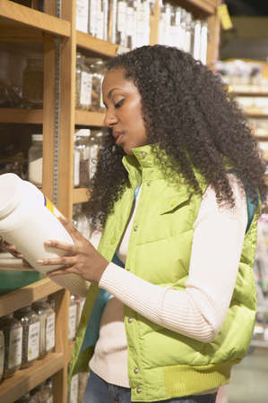 Mid adult woman looking at a price label Stock Photo - 16071560
