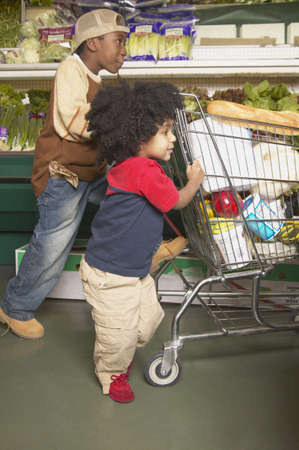 Two boys pushing a shopping cart in a supermarket Stock Photo - 16071564