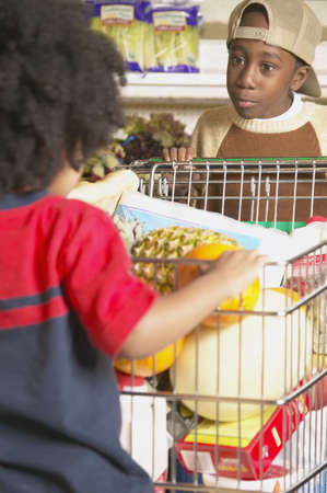 Two boys with a shopping cart in a supermarket Stock Photo - 16071565