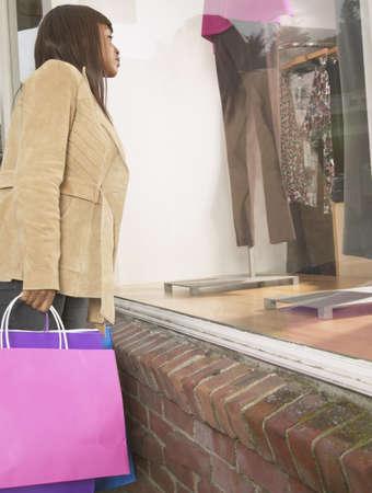 mannequin africain: Profil de côté d une jeune femme qui cherche dans un magasin LANG_EVOIMAGES