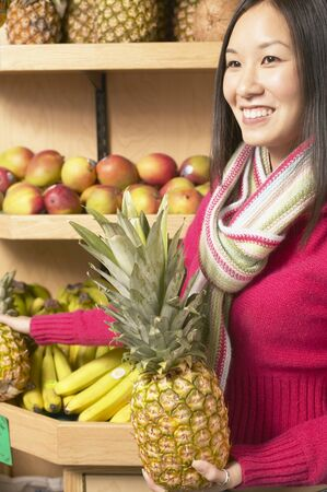 Young woman smiling holding a pineapple Stock Photo - 16071600