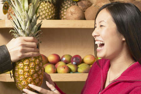 Young woman laughing holding a pineapple Stock Photo - 16071601