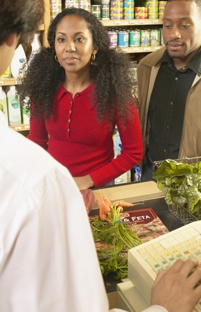 jamaican adult: Mid adult man and a young woman at a check out counter