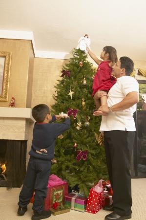 Familia decorar un árbol de Navidad Foto de archivo - 16071606
