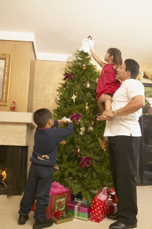 decorating christmas tree: Family decorating a Christmas tree