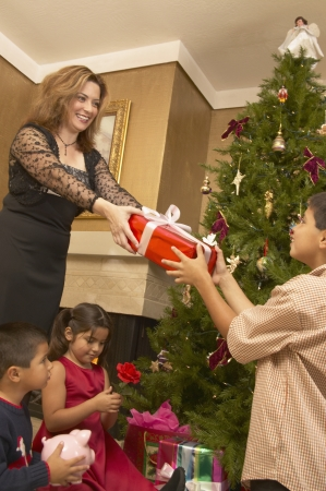 some under 18: Mother giving a gift to her son on Christmas eve
