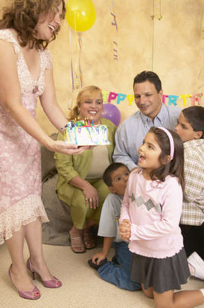 some under 18: Mother offering a birthday cake to her daughter LANG_EVOIMAGES