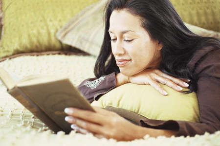 domestic: Woman reading book on bed LANG_EVOIMAGES