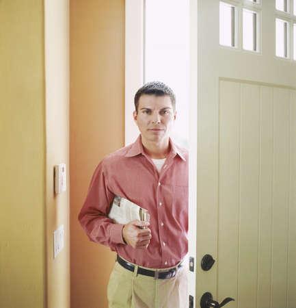 coming home: Man entering front door of home