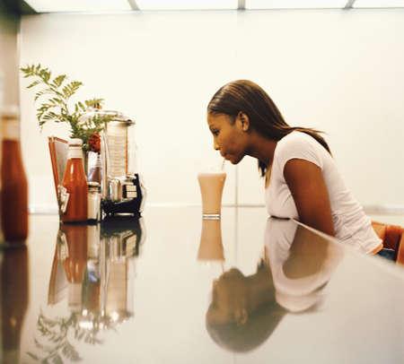 Woman drinking milkshake at diner counter Stock Photo - 16071696
