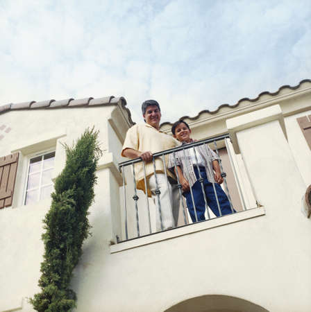 some under 18: Man and boy standing on home balcony