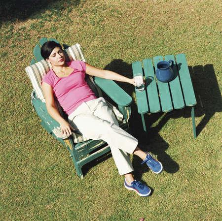 unwinding: Woman unwinding in yard with iced drink