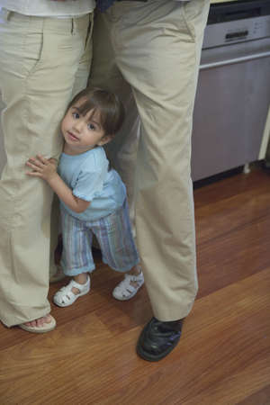 mixed age range: Toddler girl standing between legs of parents