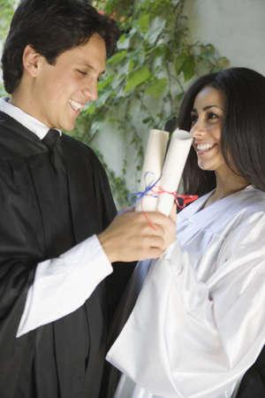 Graduating man and woman holding diplomas Stock Photo - 16071729