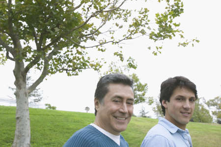 above 21: Portrait of father and son in a park LANG_EVOIMAGES