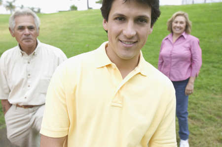 Grown son posing with parents in a park Stock Photo - 16071740