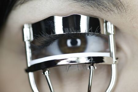 above 18: Close-up of a woman using an eyelash curler LANG_EVOIMAGES