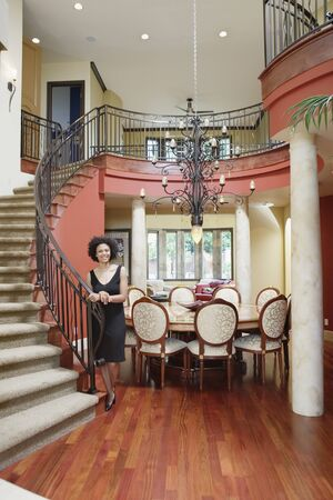 Woman standing by staircase in house Stock Photo - 16071763