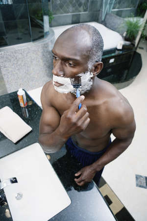 Man shaving in bathroom Stock Photo - 16071780