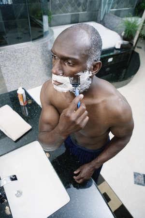 Man shaving in bathroom Stock Photo - 16071780