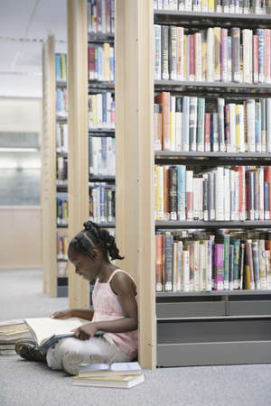 Girl reading book in library Stock Photo - 16071787