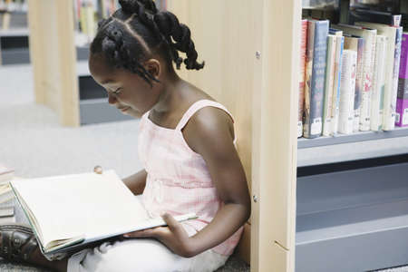 Girl reading book in library Stock Photo - 16071788