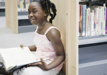 Girl holding book in library Stock Photo - 16071789