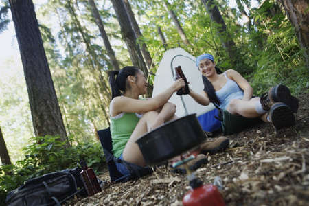 gas stove: Women relaxing at campsite LANG_EVOIMAGES