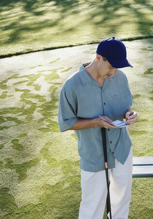 Golfer writing down score Imagens