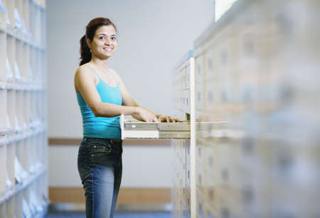 Woman standing by library file drawer