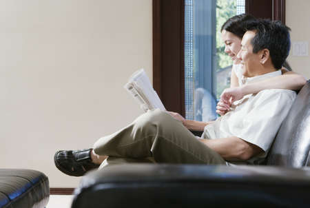 some under 18: Profile of father and daughter sitting on couch reading newspaper