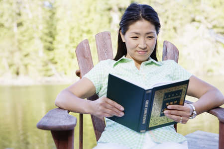 above 30: Woman sitting on deck by lake reading LANG_EVOIMAGES