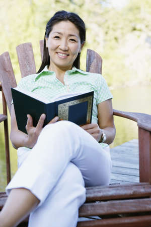 Portrait of woman sitting on deck by lake reading book Stock Photo - 16071868