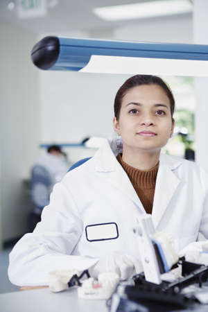 above 30: Portrait of female technician sitting at desk