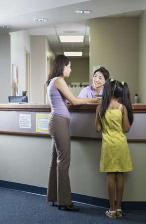 some under 18: Rear view of mother and daughter at reception desk of clinic