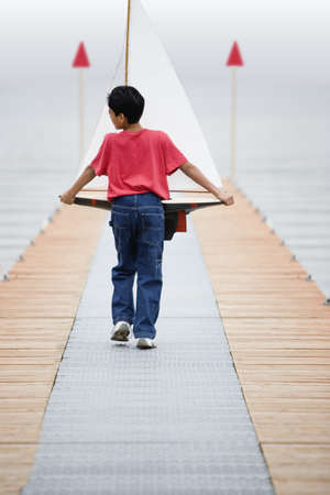 all under 18: Rear view of boy walking down pier holding toy sailboat