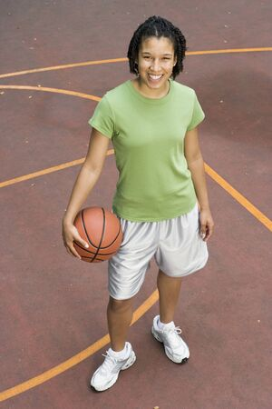 outdoor basketball court: Portrait of teenage girl with basketball on court LANG_EVOIMAGES