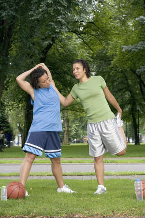 above 18: Two teenage girls stretching LANG_EVOIMAGES