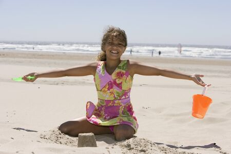 all under 18: Portrait of girl building sandcastle at beach