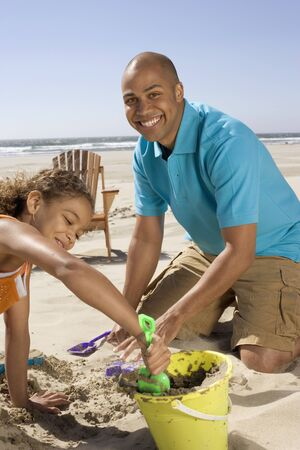 some under 18: Portrait of father and daughter playing in sand at beach LANG_EVOIMAGES