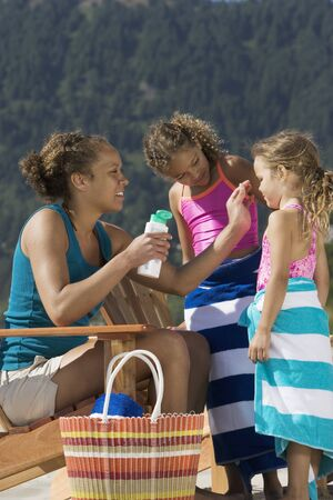 Mother applying suntan lotion to daughters at beach Stock Photo - 16071963