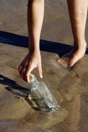 low section: Low section of girl picking up bottle on beach