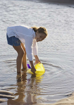 scooping: Portrait of girl scooping up water in bucket at beach