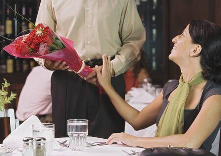 Waiter handing woman flowers at restaurant LANG_EVOIMAGES