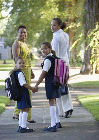 some under 18: Rear view of women and girls walking down sidewalk