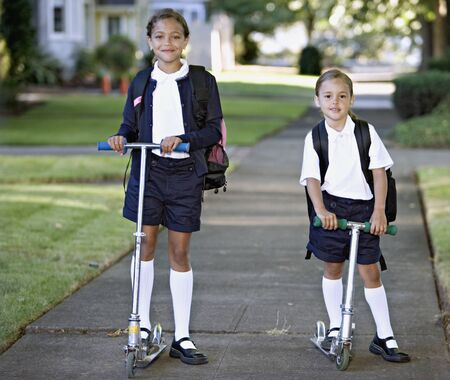 some under 18: Portrait of sisters wearing uniforms on scooters