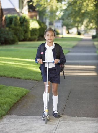 some under 18: Portrait of girl in school uniform with scooter