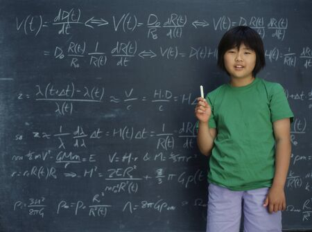 Portrait of girl holding chalk in front of chalkboard